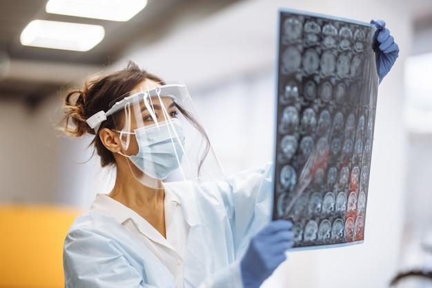 Vrouw arts controleert mri x-ray beeld van de hersenen van de patiënt in het ziekenhuis. vrouwelijke medische werker die beschermend masker en witte jurk draagt op de gang van een ziekenhuis. heath en geneeskunde concept.