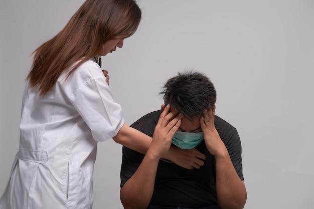 Vrouw arts controleren lichaam man patiënt ziek door stethoscoop.