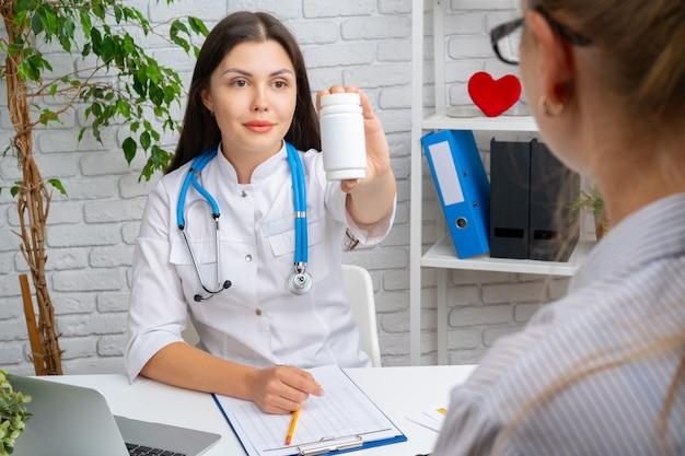 Vrouw arts die een geneesmiddel voorschrijft aan haar patiënt in het ziekenhuis