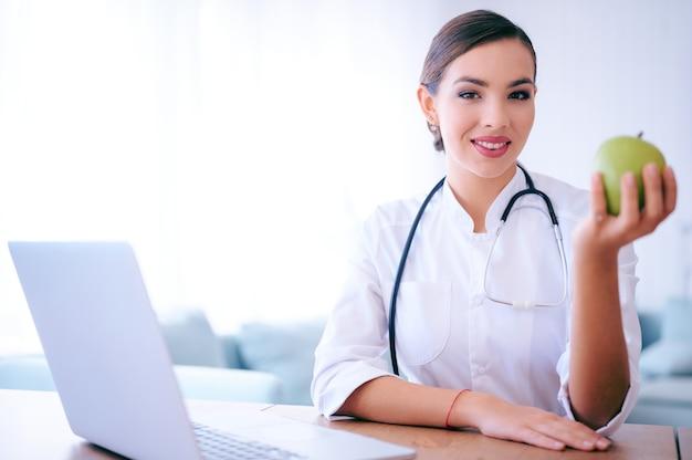 Vrouw arts die groene appel in het ziekenhuis houdt. medische gezondheidszorg voeding concept