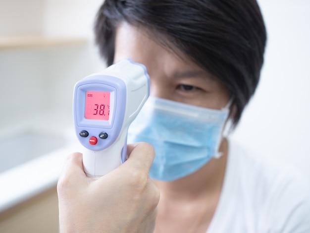 Vrouw arts die medische infrarode voorhoofdthermometer houden die lichaamstemperatuur controleren