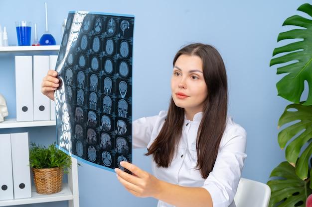 Vrouw arts die mr van de patiënt beeld in haar bureau onderzoeken