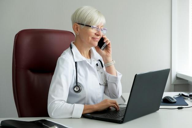 Vrouw arts die op de telefoon in het spreekkamer spreekt. raadpleegt de patiënt.