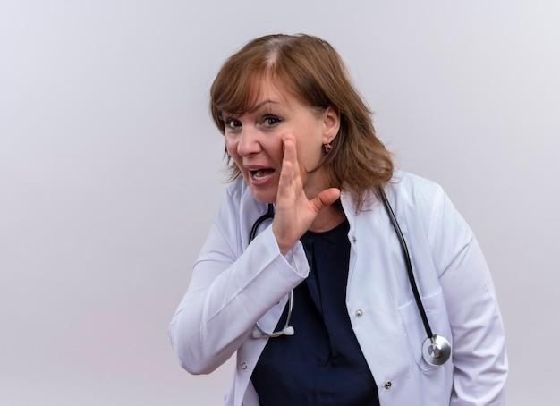 Vrouw arts die op middelbare leeftijd medische mantel en stethoscoop draagt die gefluister gebaar op geïsoleerde witte muur met exemplaarruimte doen