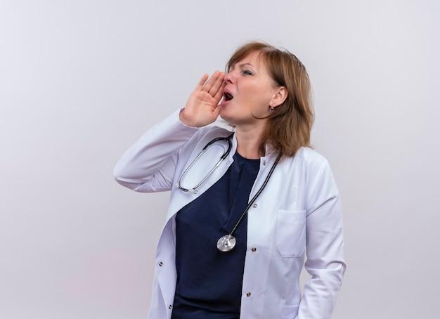 Vrouw arts die op middelbare leeftijd medische mantel en stethoscoop draagt die hand dichtbij mond op geïsoleerde witte muur met exemplaarruimte zet