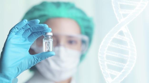 Vrouw arts die transparante glasfles met dna-pictogram binnen op haar hand houden.