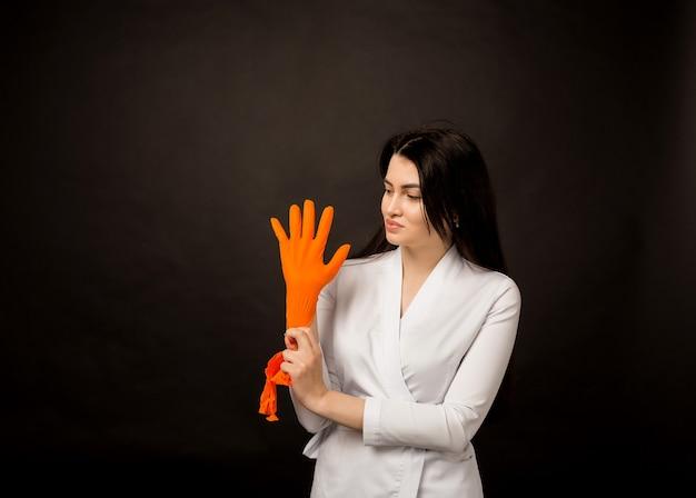 Vrouw arts draagt oranje handschoenen op zwart
