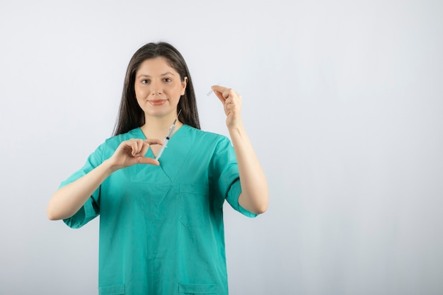 Vrouw arts dragen groene uniforme bedrijf spuit op wit.