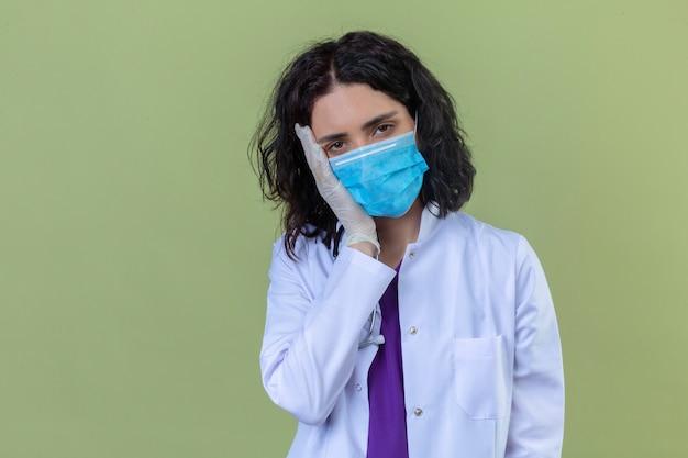 Vrouw arts dragen witte jas met stethoscoop in medisch beschermend masker op zoek moe staande met hand op wang gevoel vermoeidheid op geïsoleerde groen