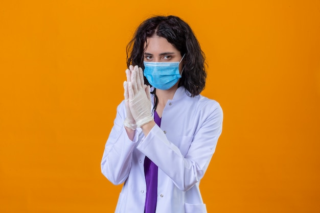 Vrouw arts dragen witte jas met stethoscoop in medische beschermend masker hand in hand samen als bidden maakt hoop gebaar staande op geïsoleerde oranje