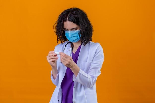 Vrouw arts dragen witte jas met stethoscoop in medische beschermend masker kijken naar digitale thermometer in handen bezorgd en nerveus staande op geïsoleerde oranje