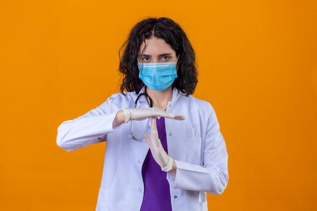 Vrouw arts dragen witte jas met stethoscoop in medische beschermend masker met een time-out gebaar met fronsend gezicht staande op geïsoleerde oranje