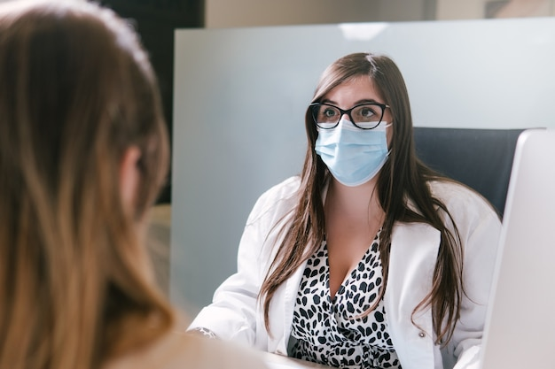 Vrouw arts gezichtsmasker dragen en praten met een patiënt op haar kantoor