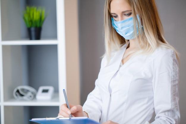 Vrouw arts in beschermend masker die bij tablet in bureau werken