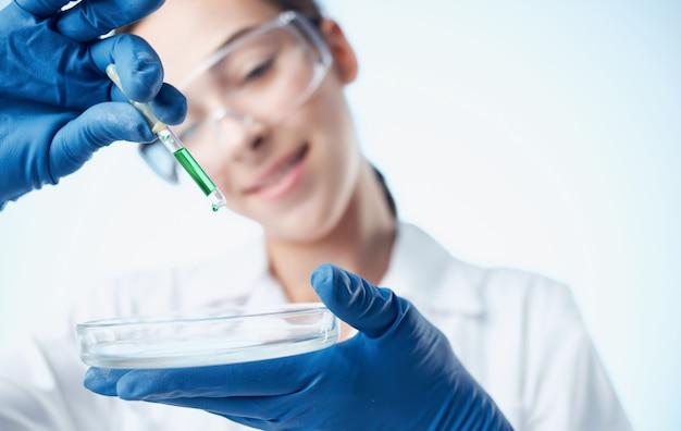 Vrouw arts in blauwe handschoenen en in een laboratorium van het chemisch element van het medische toga vaccin