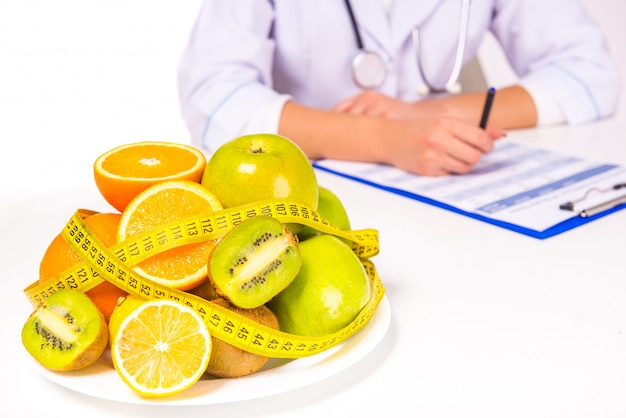 Vrouw arts in een jas met fruit