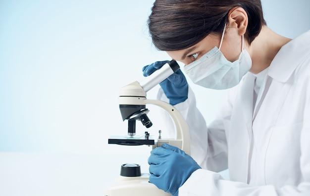 Vrouw arts in een medische jurk en handschoenen kijken door een microscoop op een tafel binnenshuis