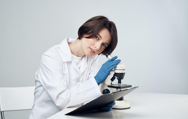 Vrouw arts in een medische jurk met een microscoop op de tafel zit op een stoel. hoge kwaliteit foto