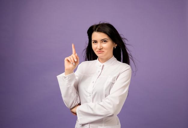 Vrouw arts in een medische jurk wijst haar vinger op paars