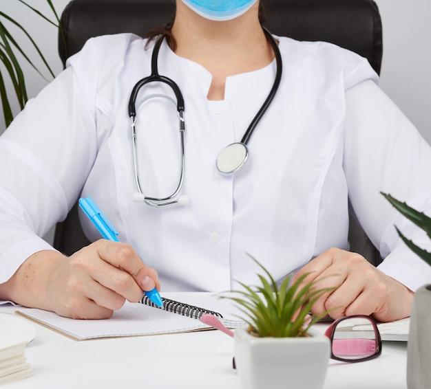 Vrouw arts in een witte jas schrijft een recept op een formulier, therapeut zit op een stoel aan een witte tafel