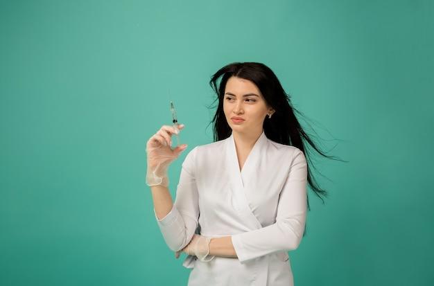 Vrouw arts in een witte jas staat in handschoenen en houdt een spuit op turkoois