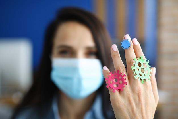 Vrouw arts in medisch masker toont bacteriën op haar hand.