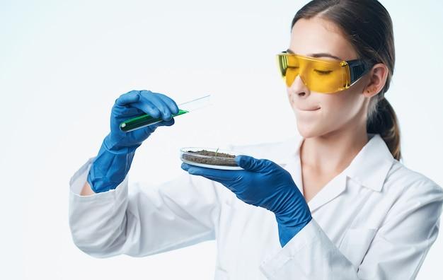 Vrouw arts in medische handschoenen en in een witte medische jas houdt kolven in haar handen documenten. hoge kwaliteit foto