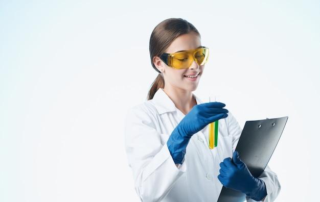 Vrouw arts in medische handschoenen en in een witte medische jas houdt kolven in haar handen documenten.