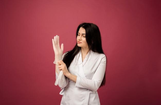Vrouw arts in wit pak draagt transparante handschoenen op rood
