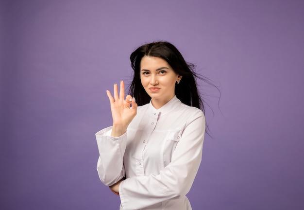 Vrouw arts in witte jas toont hand ok op paars