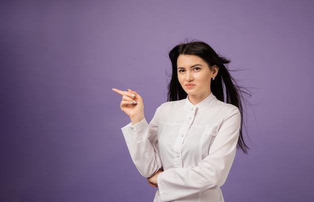 Vrouw arts in witte jas wijst vinger naar kant op paars