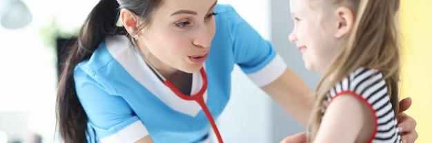 Vrouw arts luisteren met stethoscoop meisje in kliniek