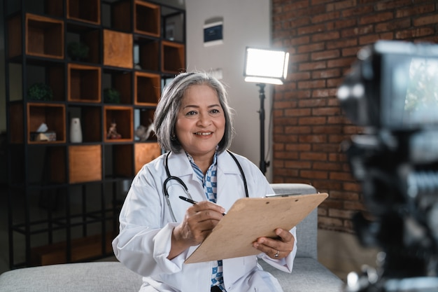 Vrouw arts maakt aantekeningen met het klembord tijdens het opnemen van video voor zijn blog