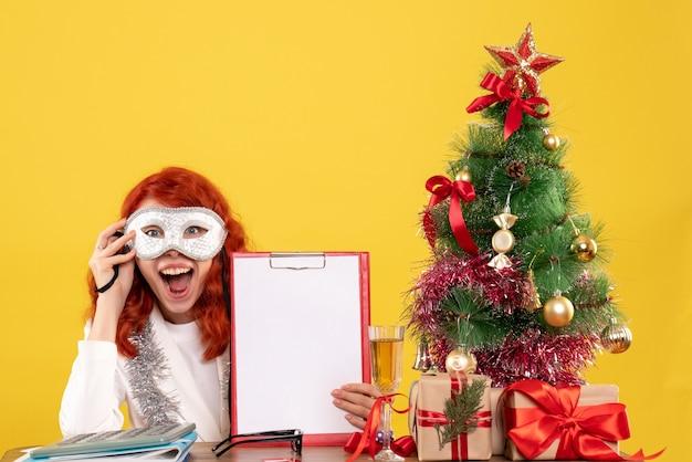Vrouw arts masker dragen rond kerstboom en presenteert op geel