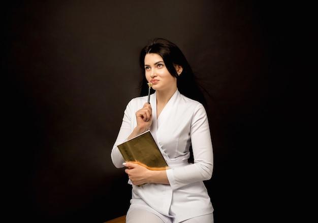 Vrouw arts met blocnote en pen op zwart
