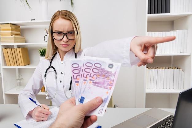 Vrouw arts met een stethoscoop die steekpenningen of smeergeld weigert, valuta euro, patiënt die geld geeft voor medische diensten, concept van corruptie