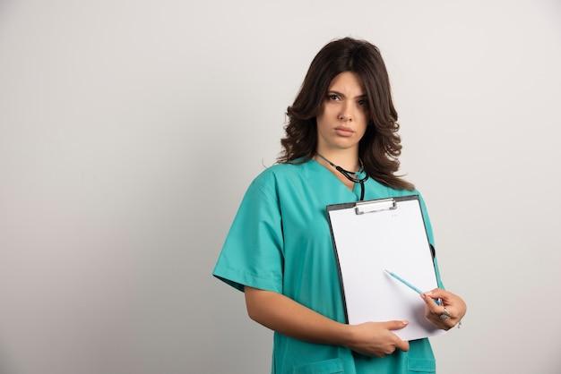 Vrouw arts met een stethoscoop die zich zorgen maakt en resultaten laat zien.