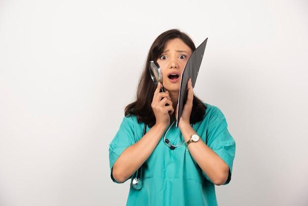 Vrouw arts met een stethoscoop en klembord camera kijken op witte achtergrond. hoge kwaliteit foto
