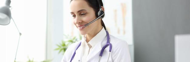 Vrouw arts met headset op zoek naar laptop scherm psychologische hulp online concept