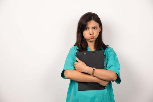 Vrouw arts met klembord dat haar adem op witte achtergrond houdt.