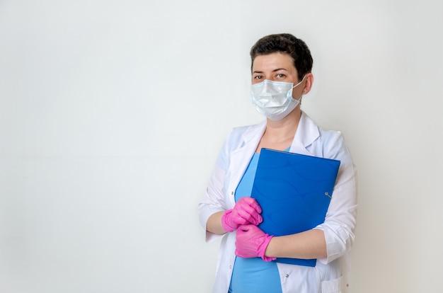 Vrouw, arts of verpleegster, gekleed in medische jurk met wegwerpmasker en handschoenen, houdt map voor documenten vast. portret van vrouwelijke arts, betrouwbare pose, op zoek naar frame. kopieer ruimte