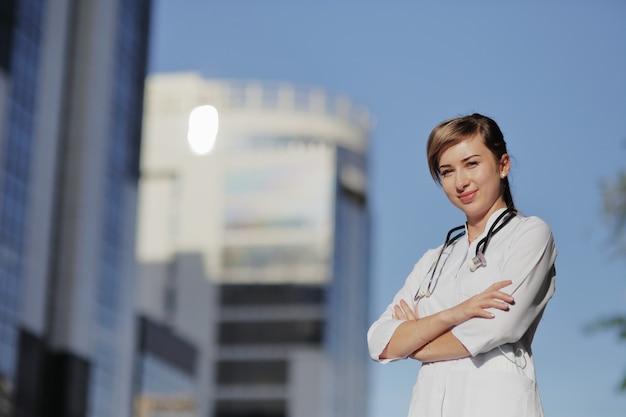 Vrouw arts op de achtergrond van gebouwen met meerdere verdiepingen van de stad