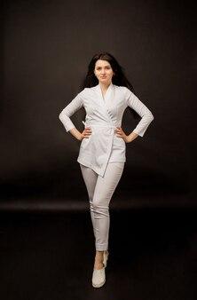 Vrouw arts van gemiddelde lengte in een wit uniform op zwart