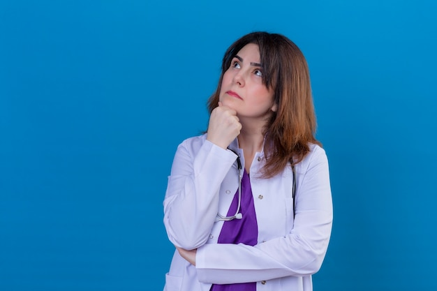 Vrouw arts van middelbare leeftijd dragen witte jas en met een stethoscoop staande met hand op kin opzoeken met peinzende uitdrukking denken over blauwe achtergrond