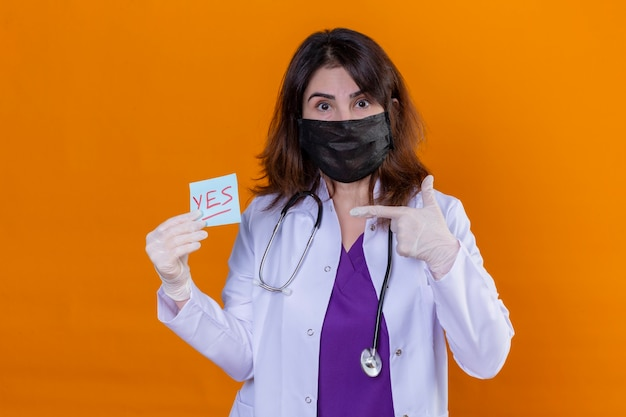Vrouw arts van middelbare leeftijd dragen witte jas in zwart beschermend gezichtsmasker en met stethoscoop houden herinneringspapier met ja woord wijst ernaar met wijsvinger over geïsoleerde oranje backg
