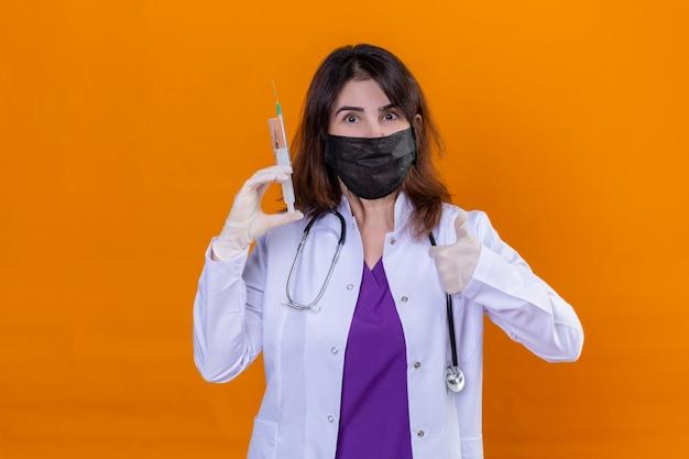 Vrouw arts van middelbare leeftijd dragen witte jas in zwarte beschermende gezichtsmasker en met stethoscoop houden spuit kijken camera positief en gelukkig weergegeven: duimen omhoog staan over oranje chtergro