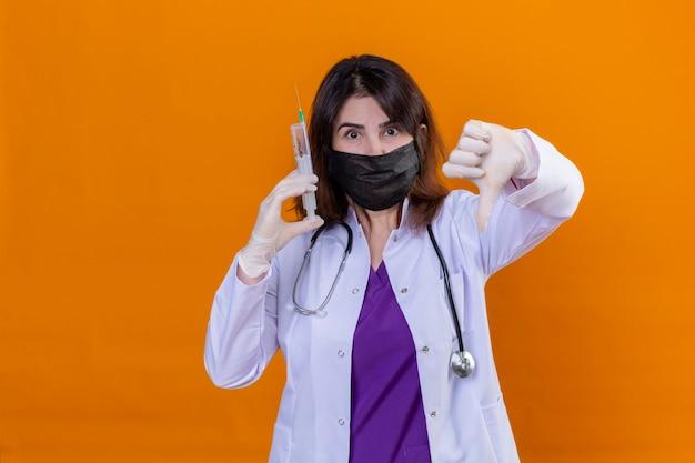 Vrouw arts van middelbare leeftijd dragen witte jas in zwarte beschermende gezichtsmasker en met stethoscoop houden spuit kijken camera weergegeven: duimen naar beneden staande over oranje achtergrond