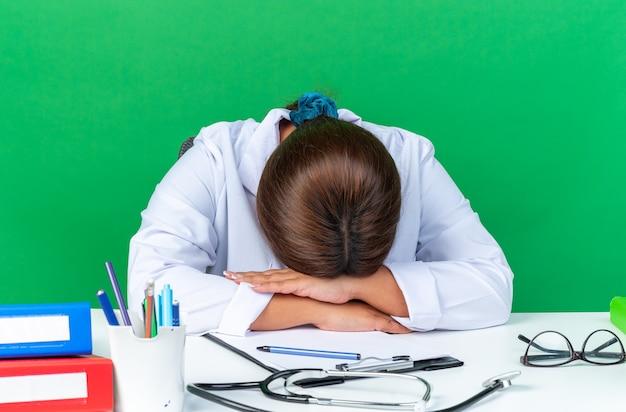 Vrouw arts van middelbare leeftijd in witte jas die er moe uitziet, met zijn hoofd op handen zittend aan de tafel met een stethoscoop over groene muur