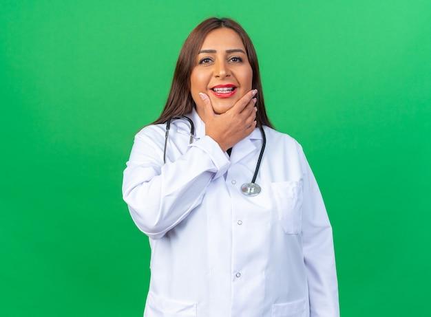 Vrouw arts van middelbare leeftijd in witte jas met stethoscoop blij en positief glimlachend vrolijk staande over groene muur