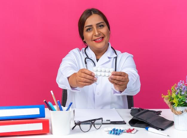 Vrouw arts van middelbare leeftijd in witte jas met stethoscoop die blister met pillen vasthoudt en glimlachend vrolijk aan tafel zit met kantoormappen over roze achtergrond